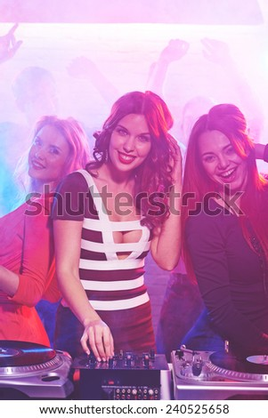 Cool girl by deejay equipment and company of friends near by - stock photo