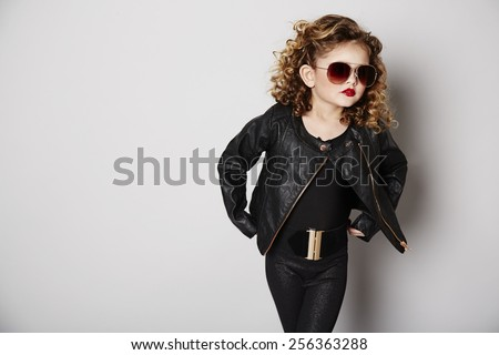 Cool girl in leather jacket and sunglasses posing, studio - stock photo