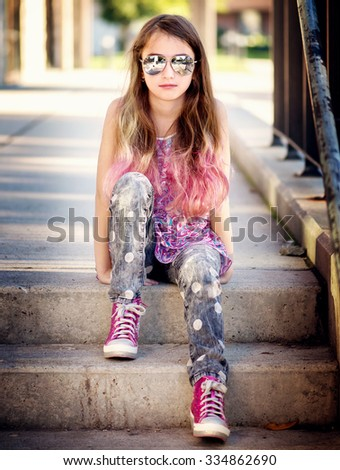 Cool girl with sunglasses and pink hair sitting on steps  - stock photo