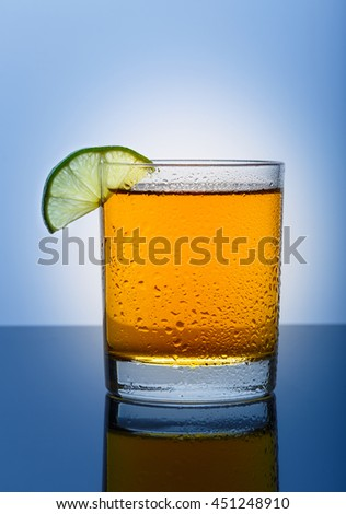 Cool glass of apple juice with lime on a blue background - stock photo