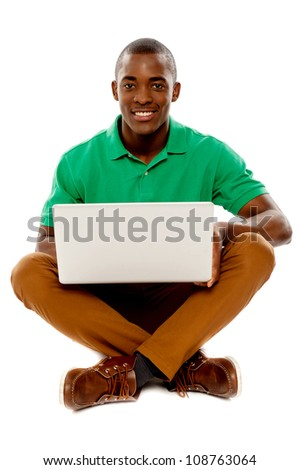Cool guy seated on floor using laptop over white background. Studio shot