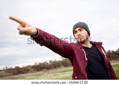 Cool handsome guy with beard at outside pointing something - stock photo