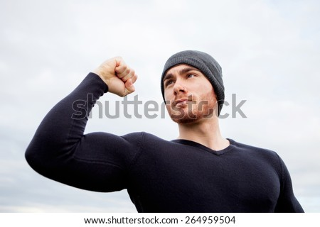 Cool handsome guy with strong arms at outside - stock photo