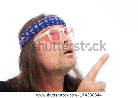 Cool hippie looking up with his blue paisley bandana and retro sunglasses - stock photo