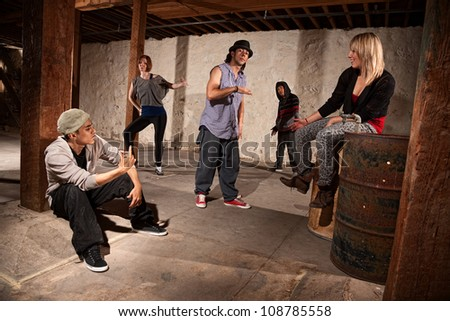 Cool Hispanic male with group of five break dancers - stock photo