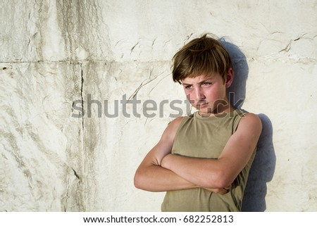 Cool Kid with arms folded against a wall