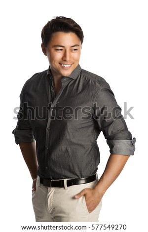 Cool laid back man wearing a grey shirt with rolled up sleeves and khaki pants, standing with a big smile against a white background.