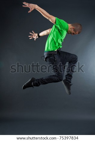cool looking dancer makes a difficult jump over white - stock photo