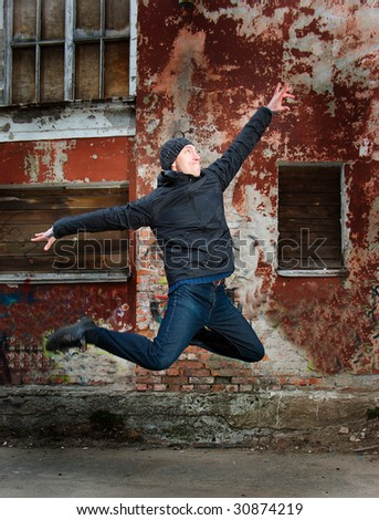 cool looking dancer posing on a grunge background with graffiti