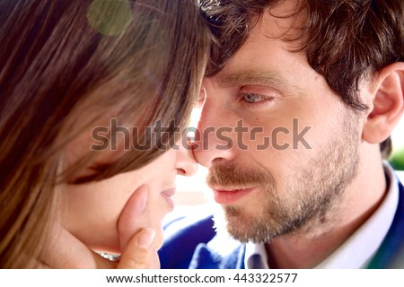 Cool man with beard touching face of girlfriend looking