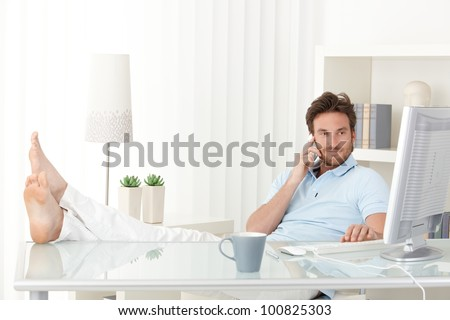 Cool man with feet up on desk making mobile phone call, typing on keyboard, smiling, looking at computer screen.