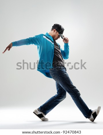 cool modern breakdancer warming up in studio,