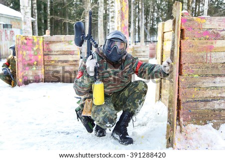 Cool paintball in winter. Two shooters behind fortifications. - stock photo