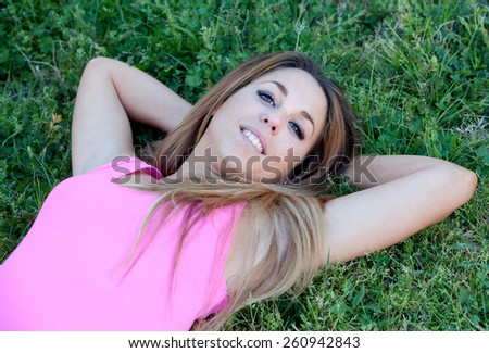 Cool pretty woman with pink t-shirt lying on the grass