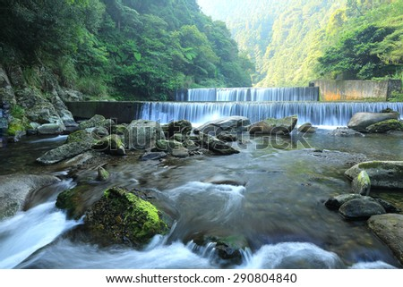 Cool refreshing cascades hidden in a mysterious forest of lush greenery ~ Fresh cascade in a mysterious forest with sunlight through the lavish greenery ~ Scenery of Taiwan - stock photo