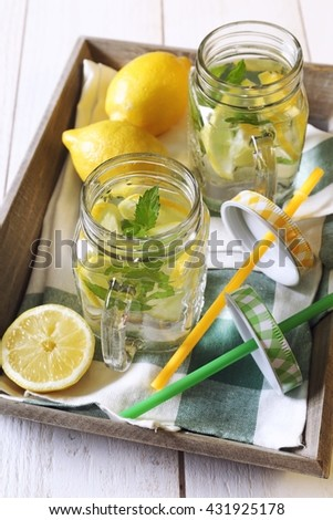 Cool refreshing drink: pure water, lemon and mint on a wooden tray - stock photo