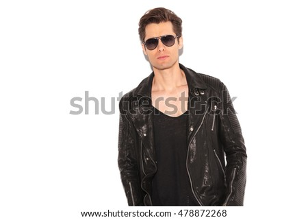 cool rock and roll man wearing leather jacket and sunglasses posing in studio