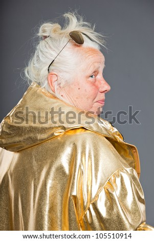 Cool senior woman wearing golden jacket. Long grey hair. Sunglasses. Studio shot. Isolated. - stock photo