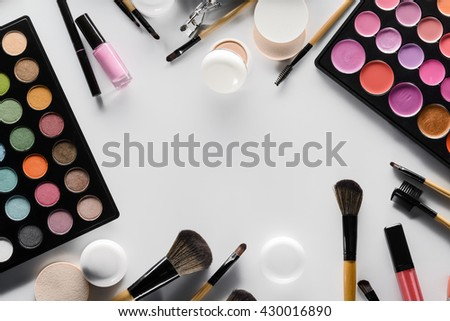 Cool set of cosmetical products in every corner of the shot. Place for lettering in the center on white table. Expensive palettes with lipstick and eyeshadows. Everything needed for cool make-up. - stock photo