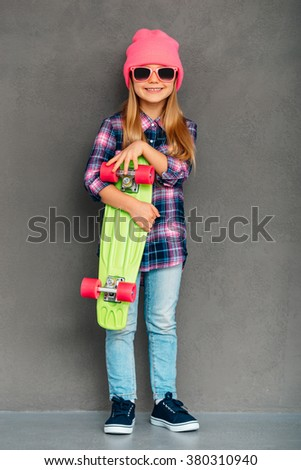 Cool skater girl. Full length of cheerful little girl in sunglasses looking at camera with smile and holding skateboard while standingagainst grey background - stock photo