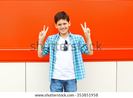 Cool smiling child boy having fun in city over red background - stock photo