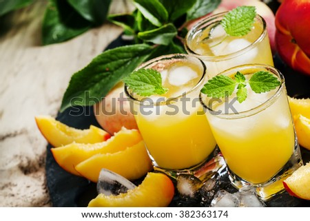 Cool summer peach juice with crushed ice, fresh peaches with leaves, selective focus - stock photo