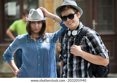 Cool teenage couple in hats posing on the street