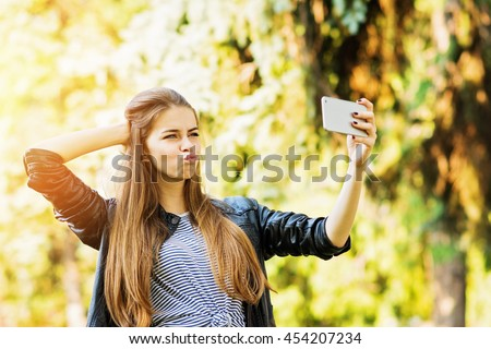 Cool teenage girl taking a selfie on smart phone in park. Closeup of beautiful young woman with long blonde hair making kissy face, posing a selfie outdoors. Natural lighting, vibrant colors. - stock photo