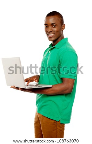Cool teenage guy surfing internet on laptop and smiling at camera