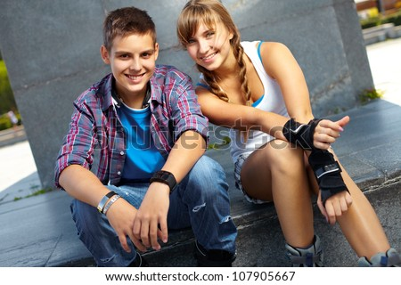 Cool teenagers hanging out together, active girl wearing roller skaters and sportswear