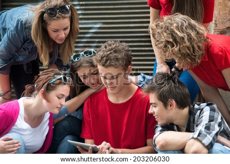 Cool teenagers reading on a tablet computer - stock photo