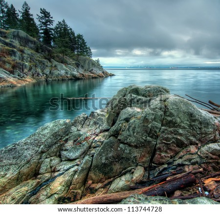 Cool tone photo along a rocky shore with the Vancouver city skyline in the distance. - stock photo