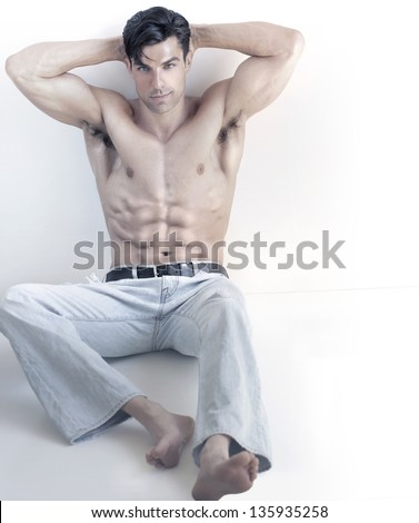 Cool toned portrait of a sexy muscular buff young male model shirtless in denim jeans relaxing with copy space and white background - stock photo
