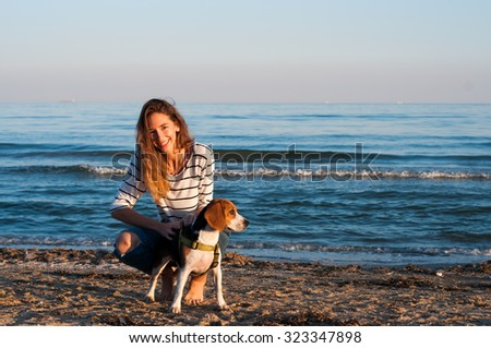 cool trendy stylish sexy blonde happy girl having fun playing with her beagle puppy dog on the beach sea background                 - stock photo