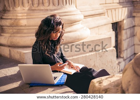 Cool urban girl using mobile technology at the city of London. - stock photo