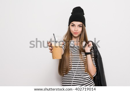 Cool urban teenage girl in black and white outfit, holding plastic coffee cup with straw. No retouch, copy space available. - stock photo