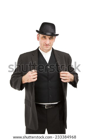 Cool white male dressed in a sharp black and white suit wearing a bowler hat and waistcoat standing holding his jacket looking smug - stock photo