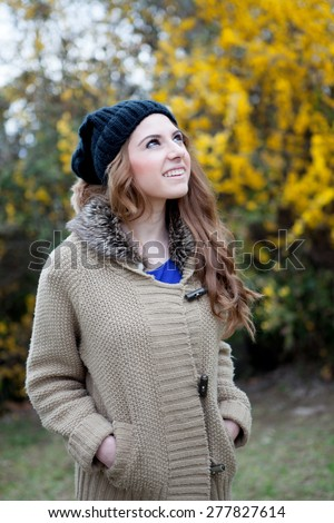 Cool woman with wool cap and a beautiful background with yellow flowers