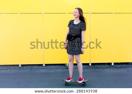 cool young and beautiful caucasian blonde teenager hipster skater girl with long gorgeous hair is having fun while skating with her cute little skate during amazing summer day on a yellow background - stock photo