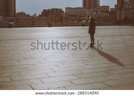cool young and beautiful caucasian blonde teenager hipster skater girl with long gorgeous hair is skating during sunset on a background of cityscape  - stock photo