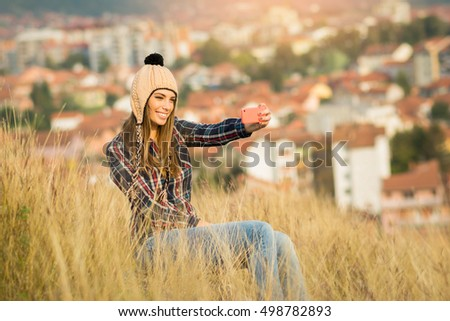 Cool young blonde millennial woman in park in autumn, sitting, wearing casual clothes and knitted beanie hat, taking a selfie on smart phone. Natural light.