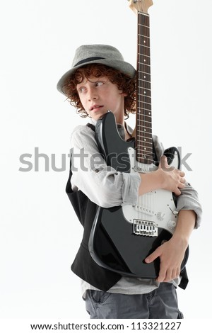 Cool young boy holding an electric guitar