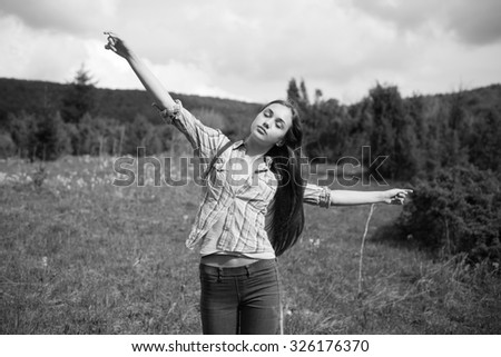 Cool young brunette enjoying nature dancing in the meadow - stock photo