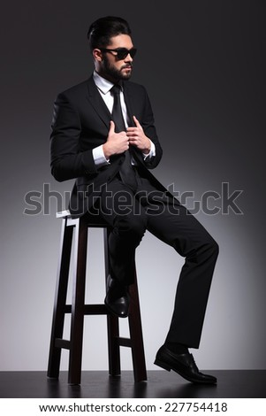 Cool young business man sitting on a stool while fixing his jacket, looking away from the camera. - stock photo