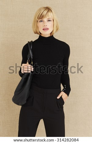 Cool young businesswoman in black, portrait - stock photo