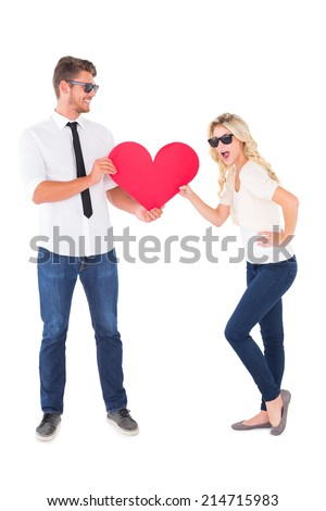 Cool young couple holding red heart on white background