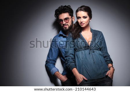 cool young couple standing together in studio