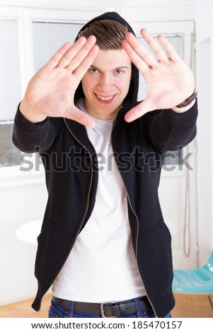 cool young guy in hooded black jacket framing his face with hands