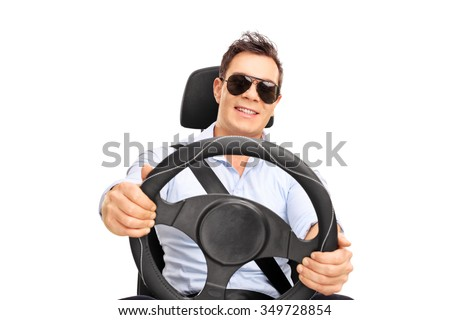 Cool young man with sunglasses pretending to drive and looking at the camera isolated on white background - stock photo
