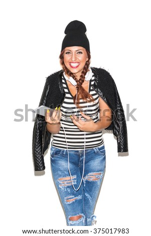 Cool young redhead woman in denim jeans, leather jacket, striped shirt and beanie hat with headphones and smartphone, smiling, isolated on white background. Vertical, medium retouch, no filter.